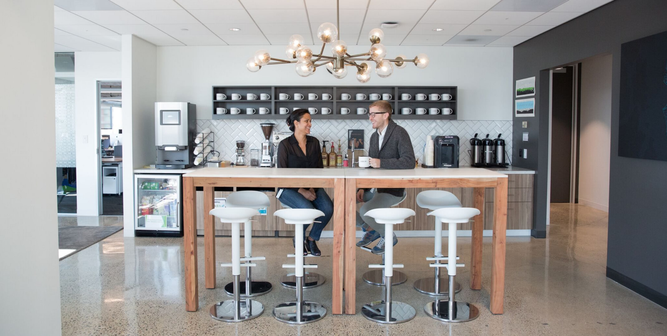 Two Employees Sit At A Table In The Break Room Of Ubers Seattle Office
