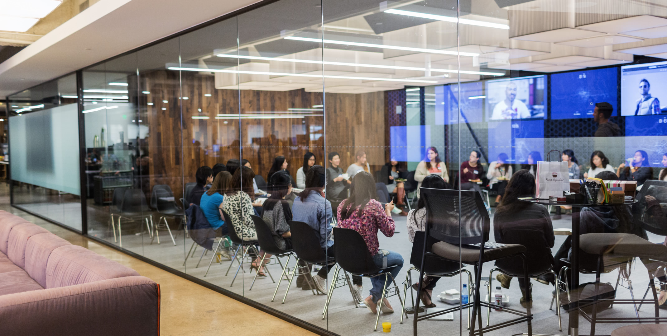 Employees In Conversation While A Large Glass Conference Room Ubers San Francisco Headquarters